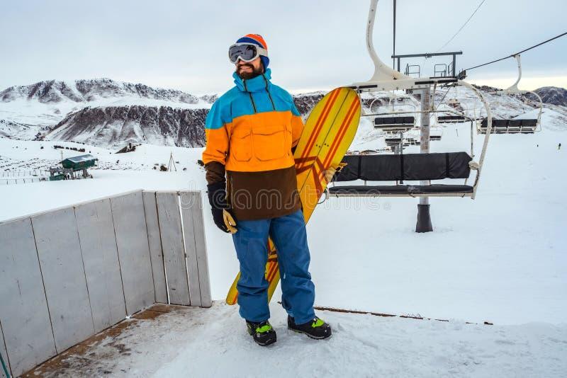 手段滑雪 有一个雪板的一个人在他的手上在驾空滑车乘驾附近站立 库存图片