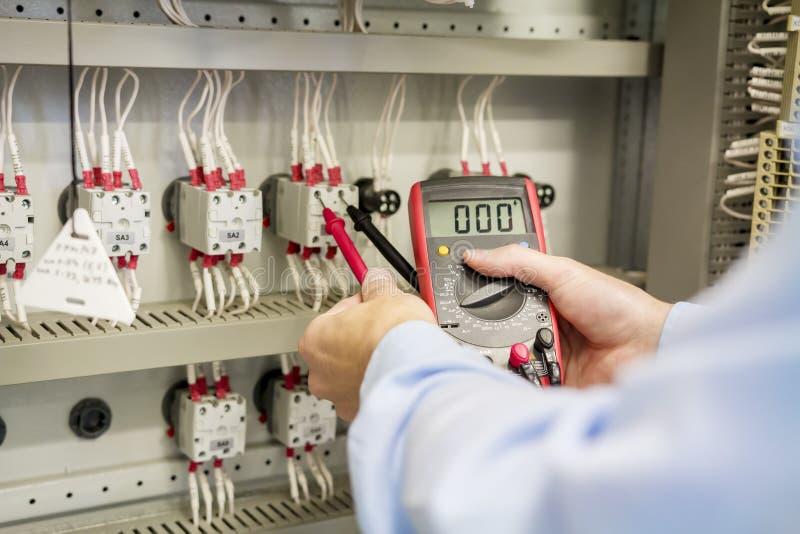手特写镜头有多用电表的在电子控制板 工程师测试电子自动化箱子 免版税库存图片