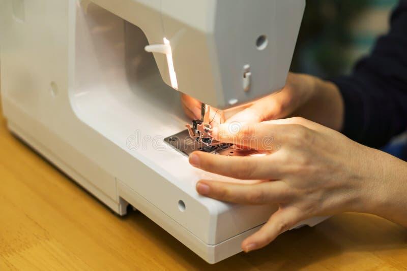 手特写镜头一个少妇,花费螺纹一台缝纫机在 库存照片