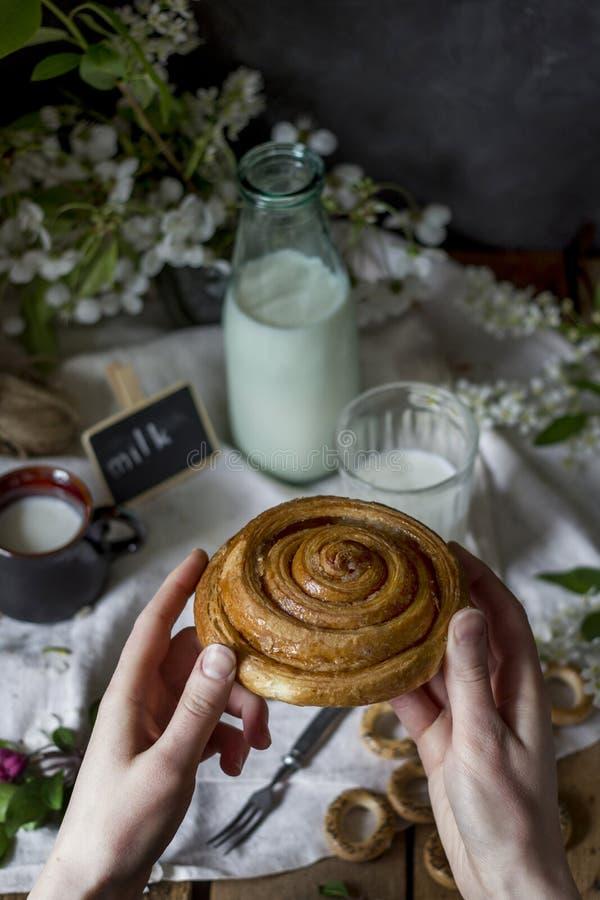 手用甜小圆面包和牛奶 库存图片