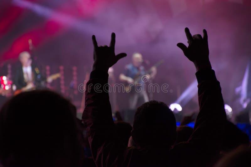 手由人群上升了在生活摇滚乐音乐会 愉快的爱好者背景 观众手和光在音乐会 库存照片
