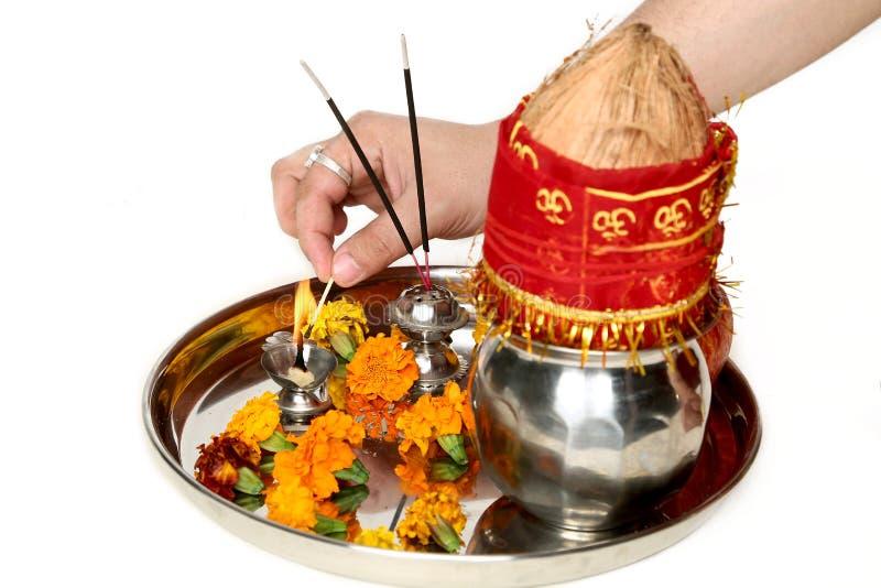 手的图片烧在美丽的pooja thali的diya 免版税库存图片