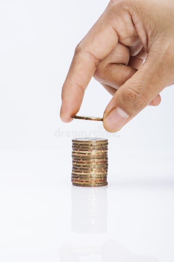 手的图象投入了硬币对堆硬币在白色背景背景挽救概念 免版税库存照片