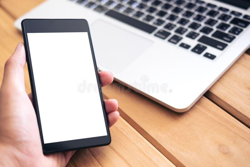手的大模型图象拿着有空白的白色屏幕的黑手机和银上色在葡萄酒木桌上的膝上型计算机 免版税库存照片