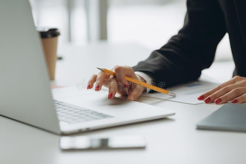手的特写镜头图象使用和接触在桌上的膝上型计算机触感衰减器 工作在现代办公室 库存图片