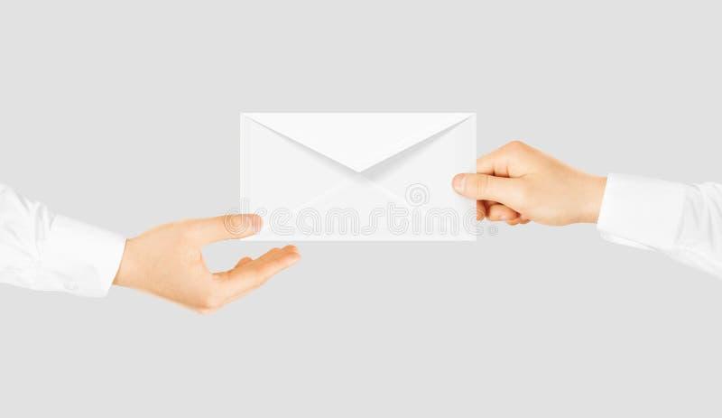 给手的白色空白的信封 消息送介绍 免版税库存照片