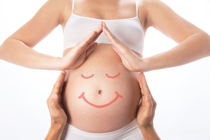 从手的议院在怀孕的腹部附近 库存照片