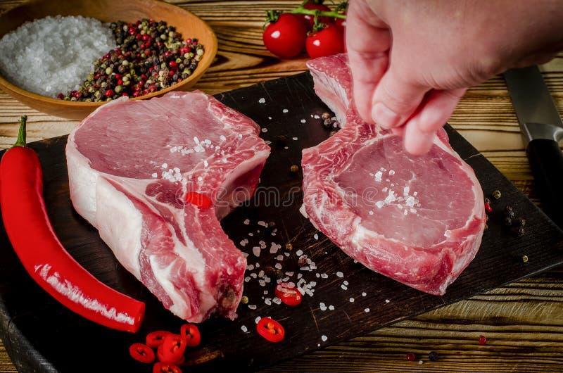 手盐肉牛排 未加工的使有大理石花纹的肉牛排,胡椒,草本,大蒜,老木背景 文本的空间 牛肋骨眼睛牛排 免版税库存照片