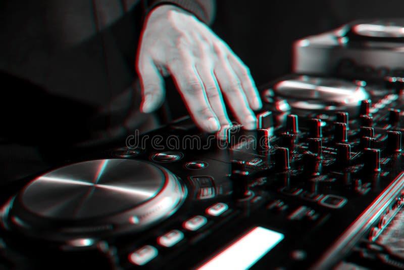 手移动在音乐控制板的DJ控制器在夜总会 免版税库存图片