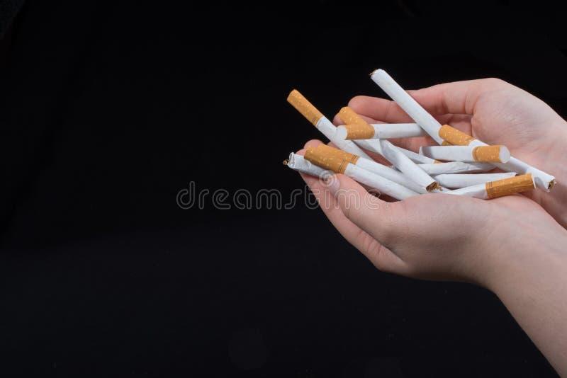 手给在黑背景的香烟 免版税库存照片