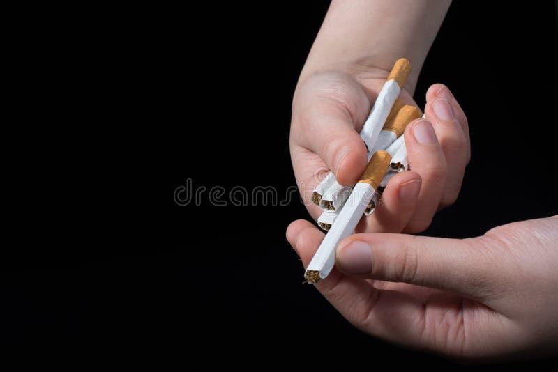 手给在黑背景的香烟 免版税图库摄影