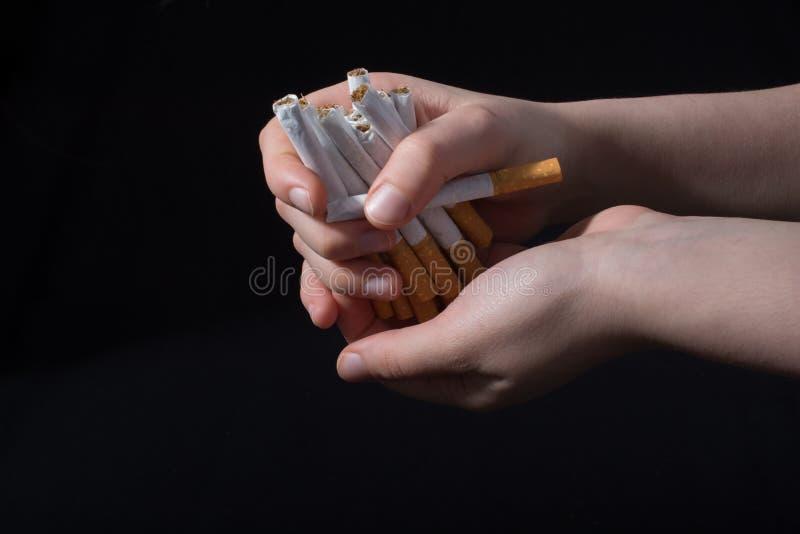 手给捆绑在黑色的香烟 库存图片