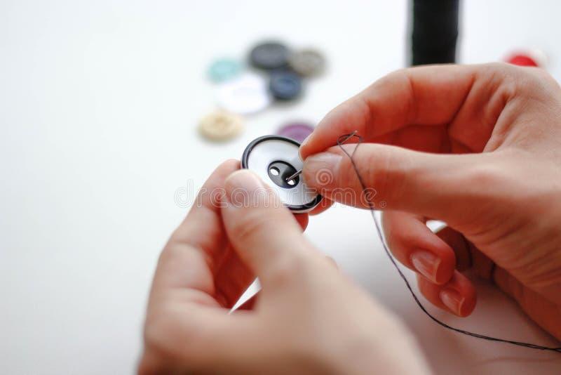 手缝合有针和螺纹的一个按钮 特写镜头 在a 免版税库存图片