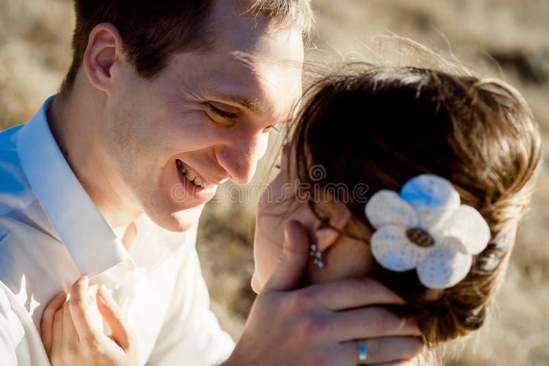 手美丽的新娘的面孔关闭的英俊的新郎举行 免版税库存图片