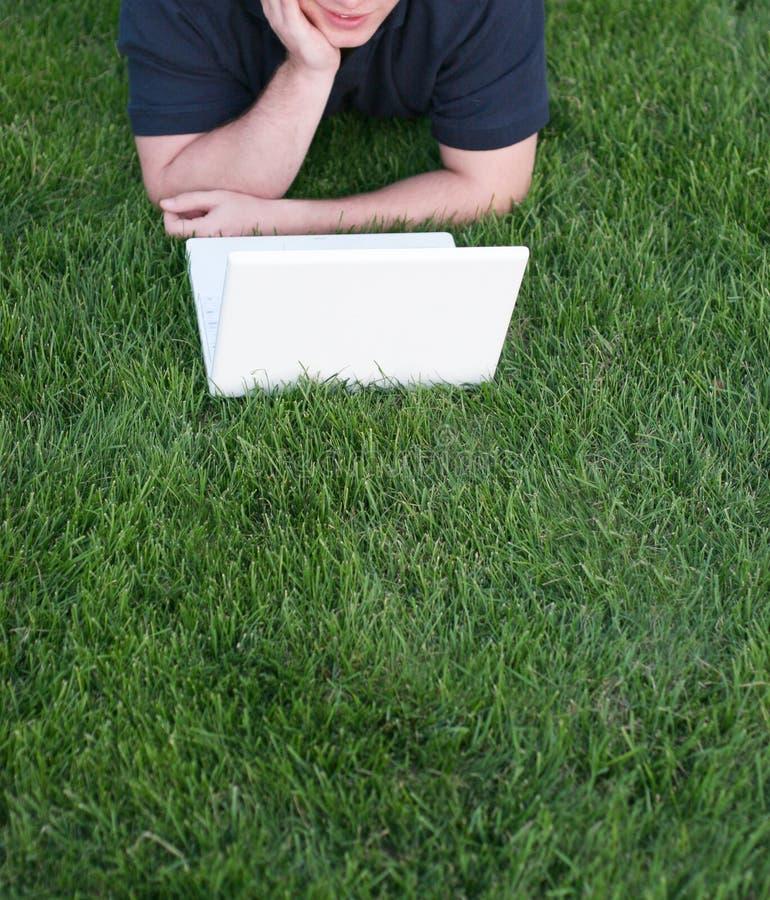 手肘膝上型计算机草坪 图库摄影