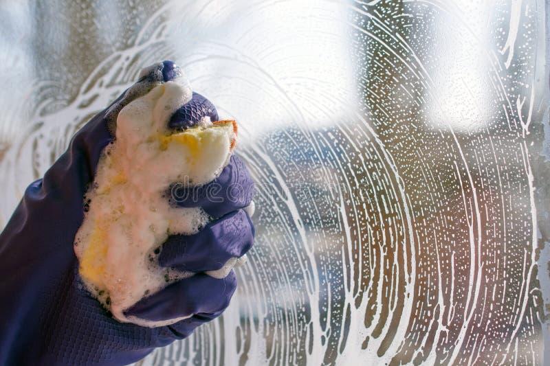 手蓝色手套洗涤窗户清洁服务 库存照片