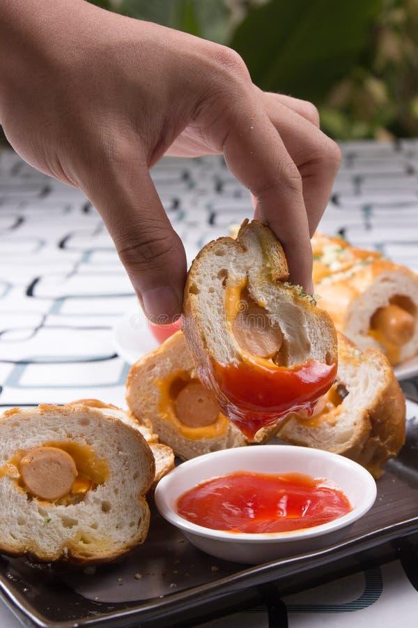 手被投入的香肠面包用番茄酱和可乐喝 免版税库存照片
