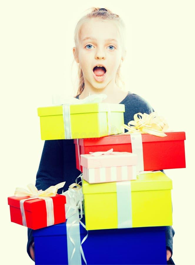 手许多的白肤金发的女孩藏品有礼物的箱子在被隔绝的背景 库存照片
