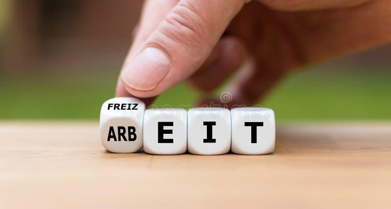 手转动一个模子并且改变德国词'Arbeit '工作'用英语到'Freizeit '悠闲时间'用英语 免版税库存图片