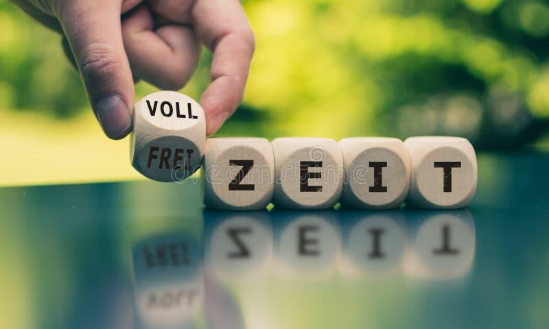 手转动一个立方体并且改变德国词'Freizeit '悠闲时间'用英语到'Vollzeit '全天工作'i 库存图片