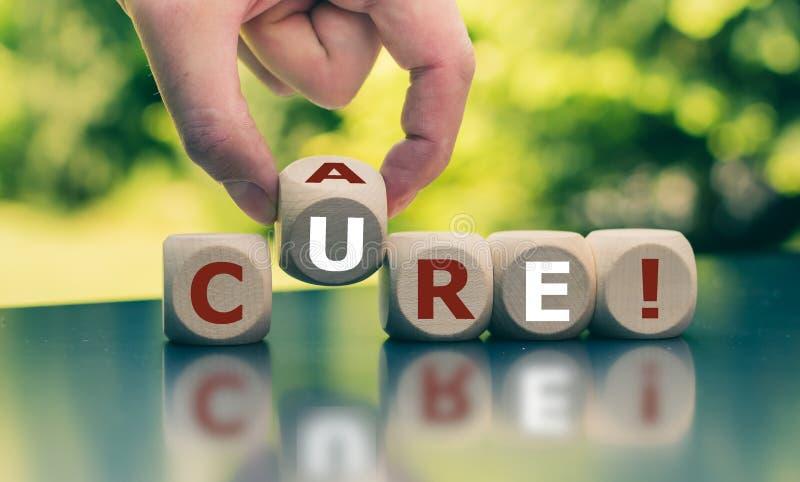 手转动一个立方体并且改变词'关心''治疗' 库存图片