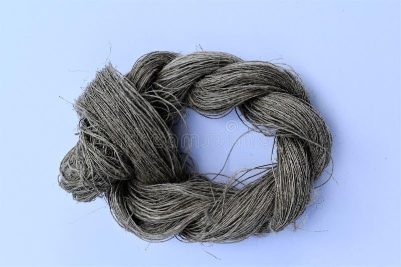 手转动的未染色的线亚麻布丝球特写镜头  纤维 库存照片