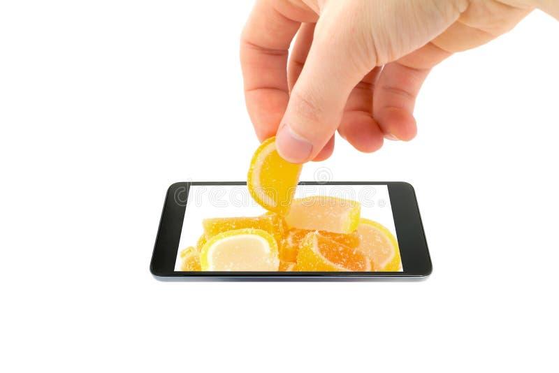 手采取橘子果酱以超出智能手机的屏幕范围的橙色切片的形式,隔绝在白色背景 免版税库存图片
