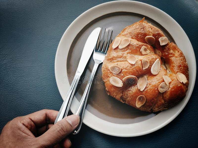 手采摘刀子和叉子吃新月形面包用在上面的切的杏仁 免版税库存图片