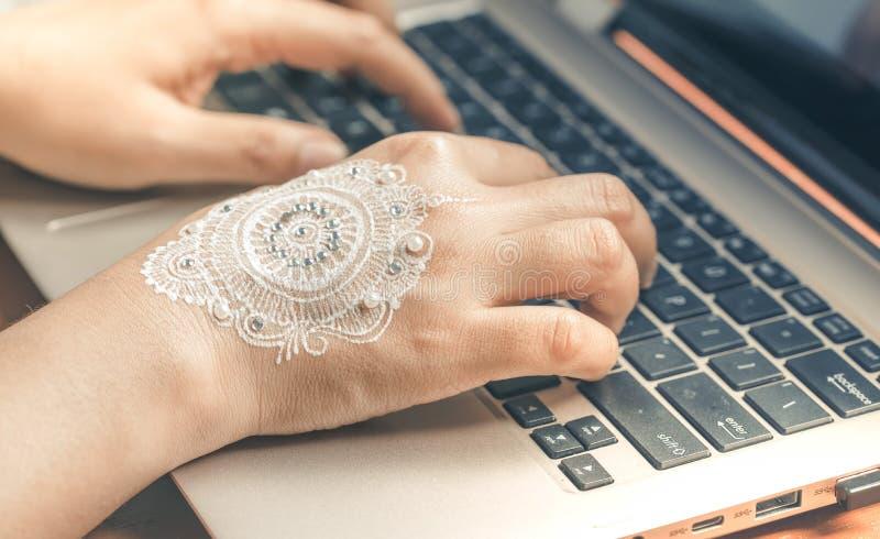手键入的膝上型计算机键盘 有坛场无刺指甲花艺术的妇女手 免版税库存照片