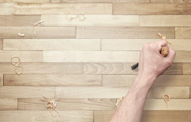 手雕刻 凿子在手中木表面上 免版税库存照片