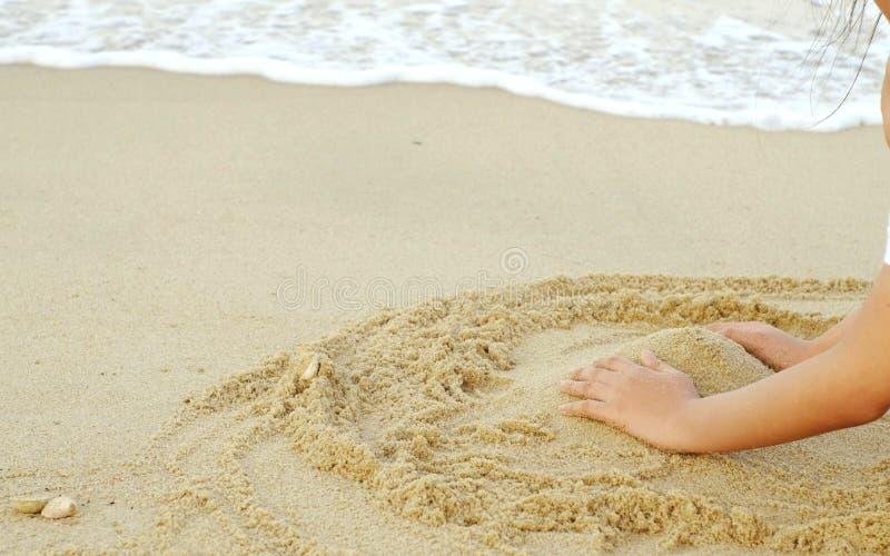 手,海滩,含沙和海在假日 免版税库存照片