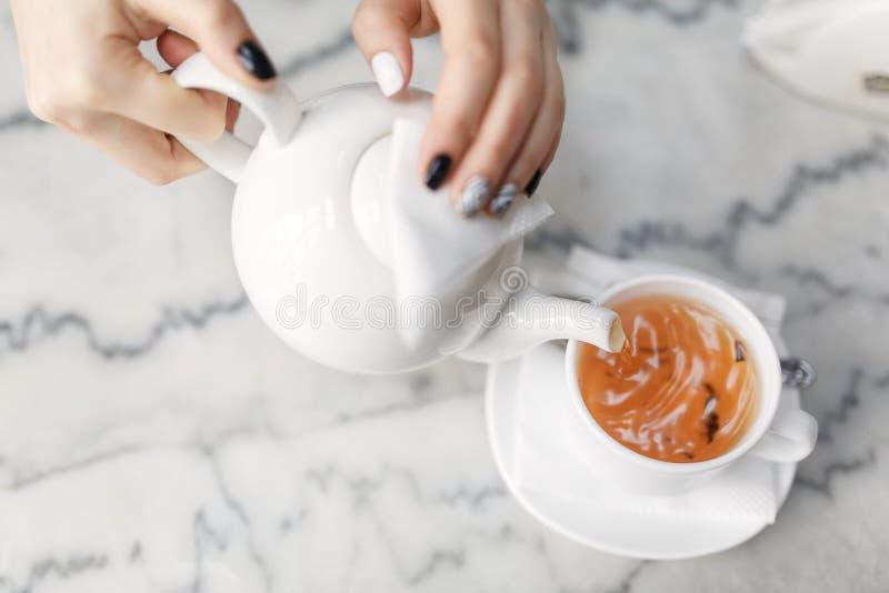 手,茶壶,一杯绿茶 图库摄影