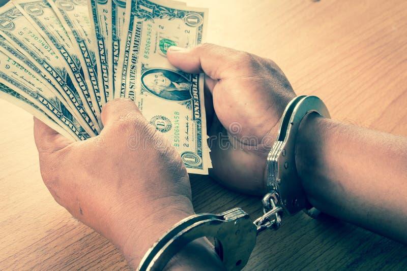 手年轻人在扣上手铐的举行金钱 库存图片