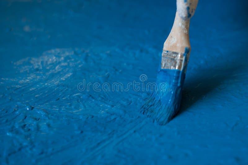 手以手套黄色被绘蓝色与骨头,关闭 库存照片