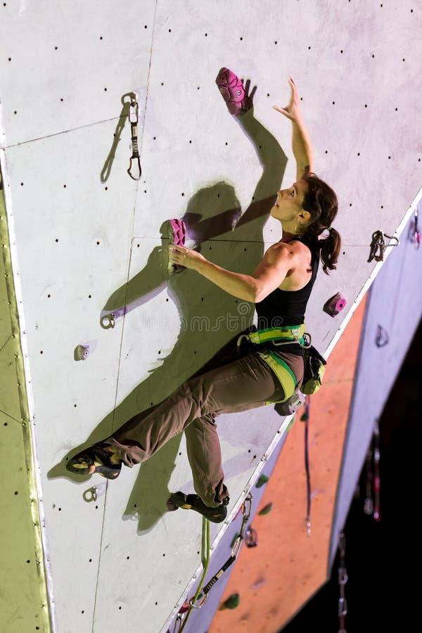 扎根在上升的墙壁上的女运动员在晚上 免版税库存图片