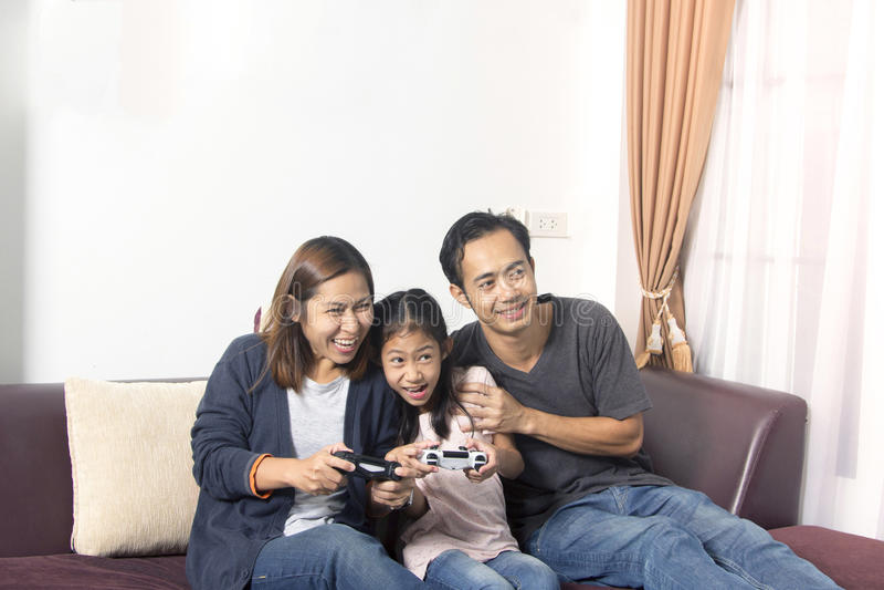 打一个电子游戏的愉快的亚洲家庭 免版税库存照片