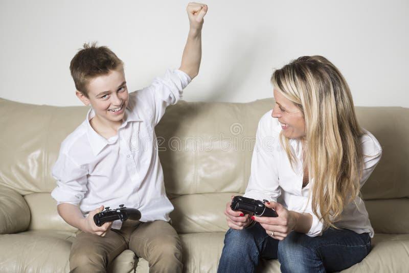 打一个电子游戏的母亲和孩子 免版税库存照片