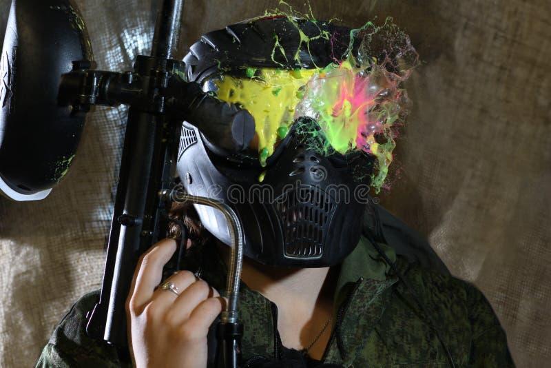 打一危险迷彩漆弹运动的面具的妇女 免版税库存图片