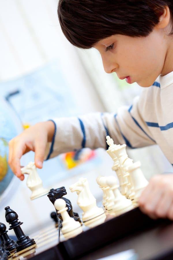 打一盘棋的男孩 免版税库存图片