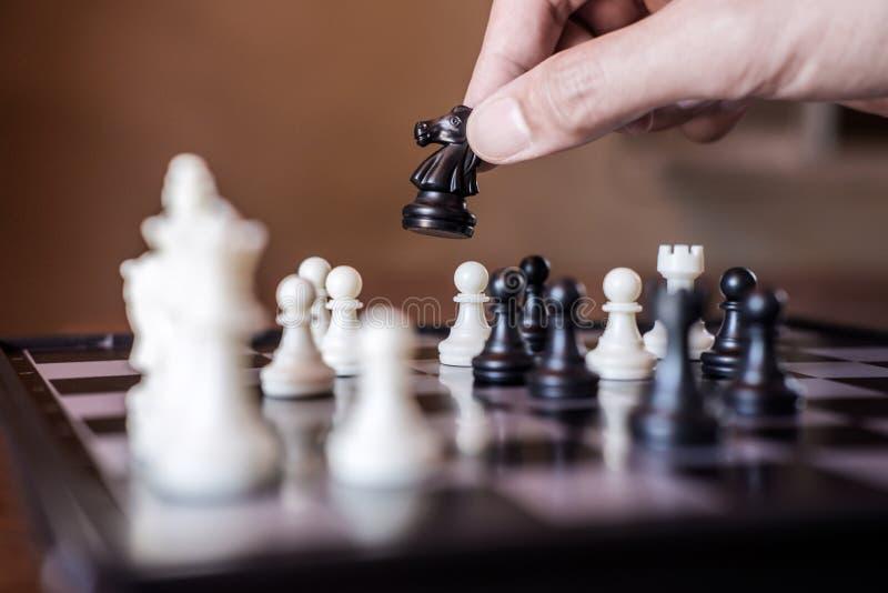 打下棋比赛的确信的商人用途马棋子黑色的手对发展分析新的战略计划,事务 免版税库存照片