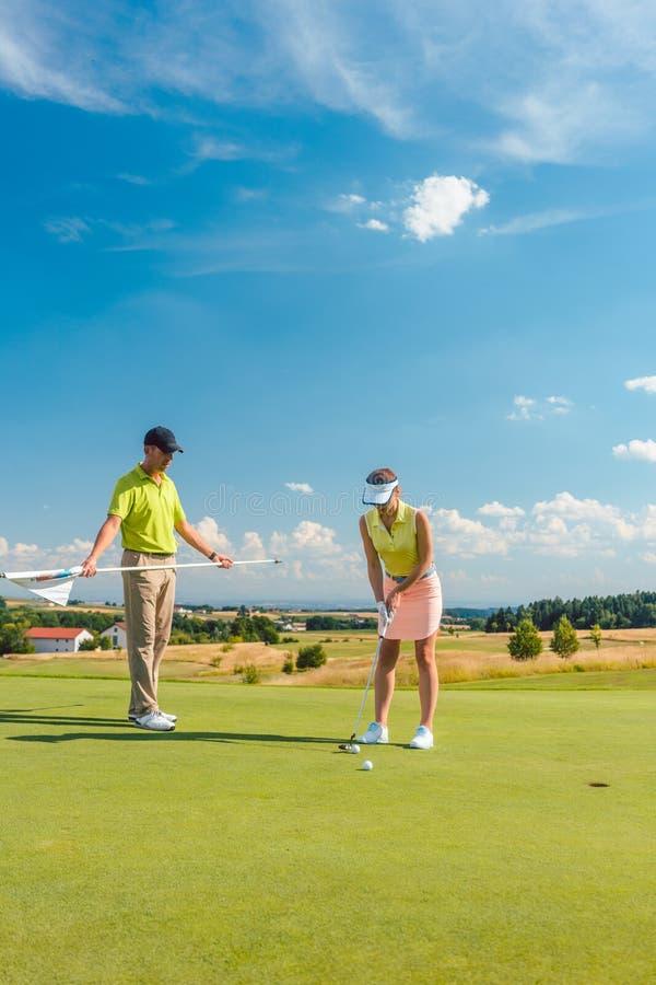 打与她的男性比赛伙伴的全长妇女职业高尔夫球 免版税库存照片