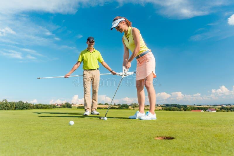 打与她的男性m的全长妇女职业高尔夫球 库存照片