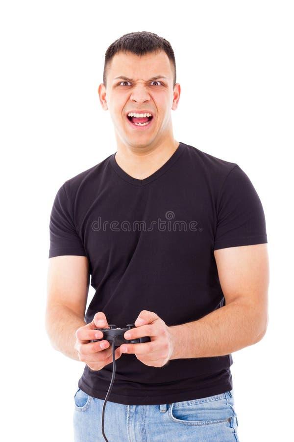 打与控制杆的被注重的英俊的人电子游戏在手上 库存照片