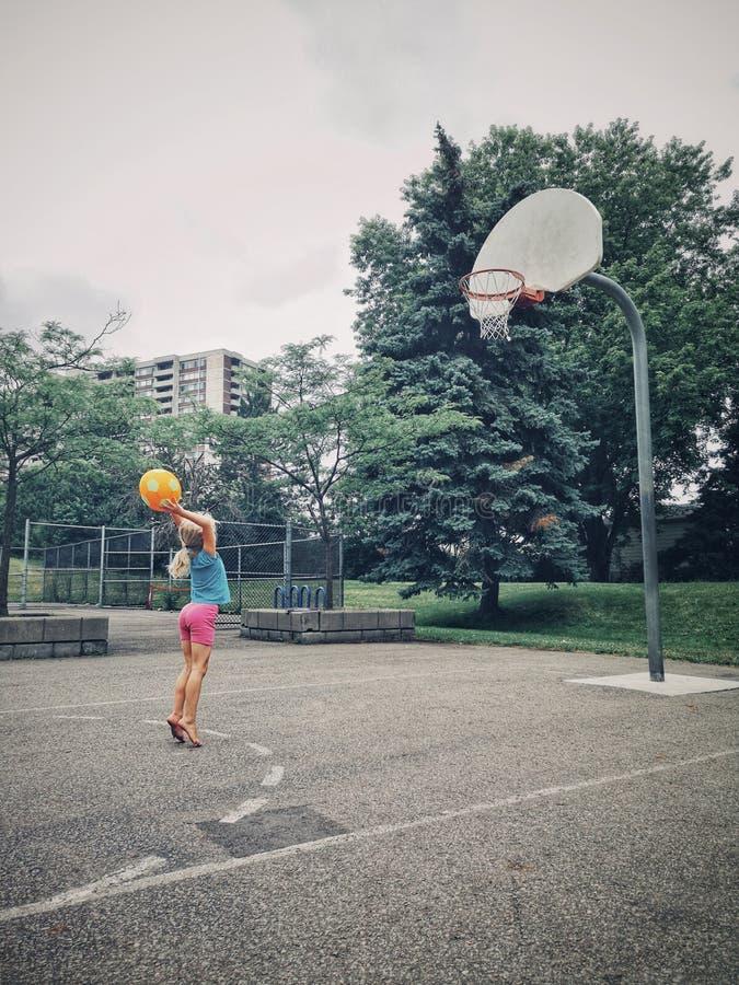打与橙黄色球的儿童女孩篮球 免版税库存照片