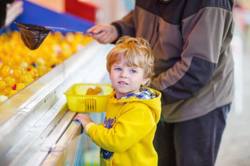打与橡胶鸭子的小逗人喜爱的孩子男孩比赛在市场 库存图片