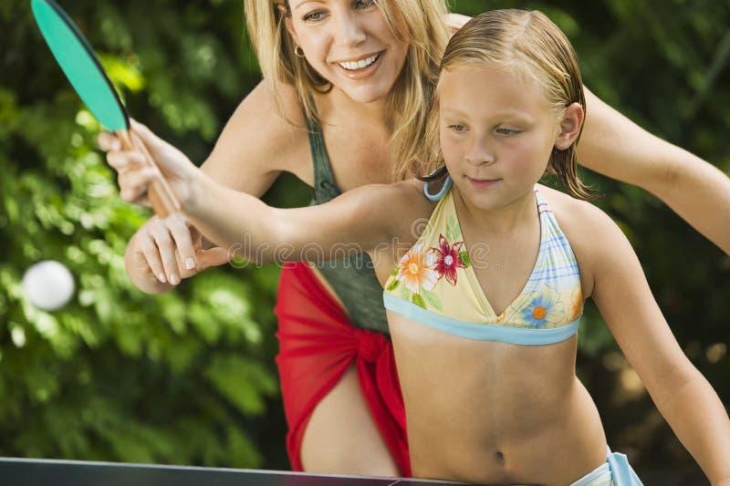 打与母亲的女孩乒乓球 图库摄影