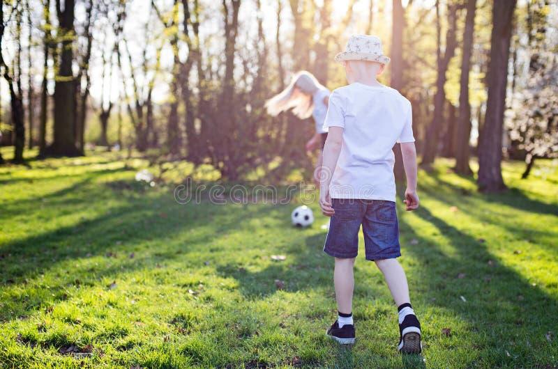 打与母亲的孩子球在公园 库存照片