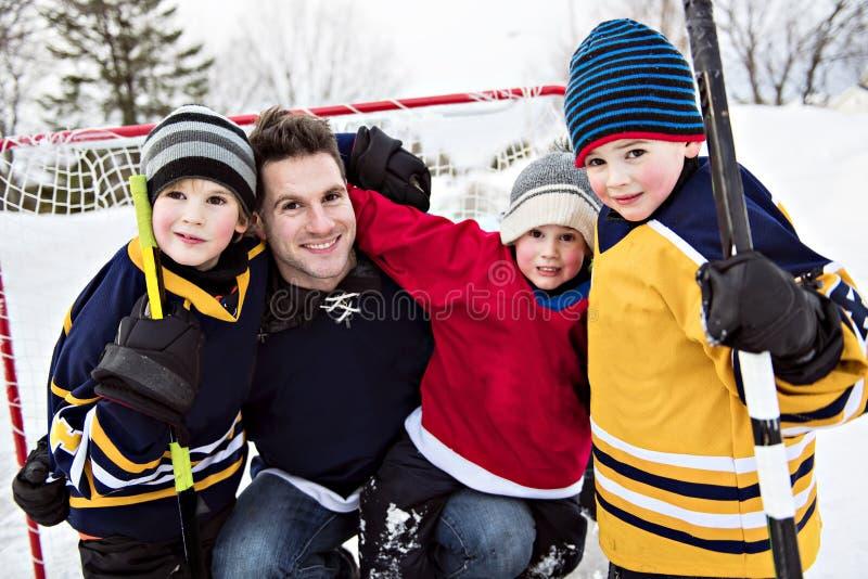 打与父亲的愉快的滑稽的孩子曲棍球在冬天季节的街道上 库存图片