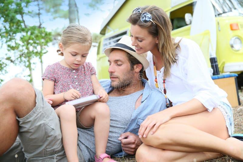 打与父母的小女孩电子游戏在野营的地方 库存图片