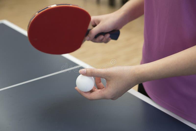 打与球拍和乒乓球的妇女乒乓球 免版税库存图片